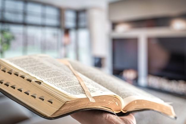 Um homem segura uma bíblia contra a parede da sala de estar. Foto gratuita