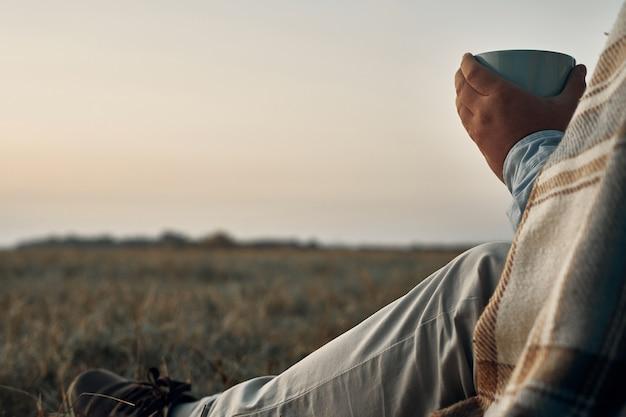 Um homem segura uma caneca nas mãos e olha para o amanhecer. viajante, nascer do sol. Foto Premium