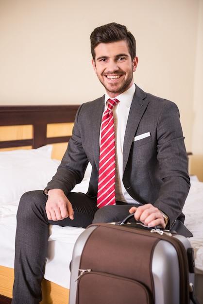 Um homem senta-se em um hotel com uma mala e sorrisos Foto Premium