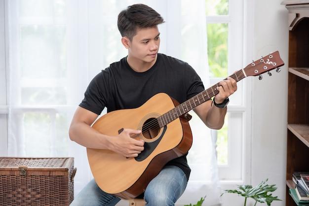 Um homem sentado e tocando violão em uma cadeira. Foto gratuita