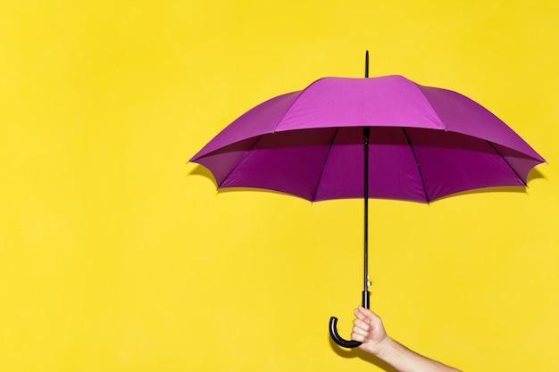 Um homem tem na mão um guarda-chuva roxo Foto Premium