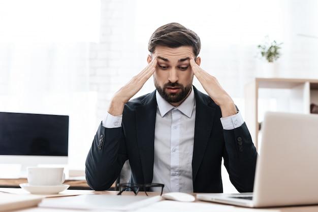 Um homem tem uma dor de cabeça ele mantém as mãos na cabeça Foto Premium