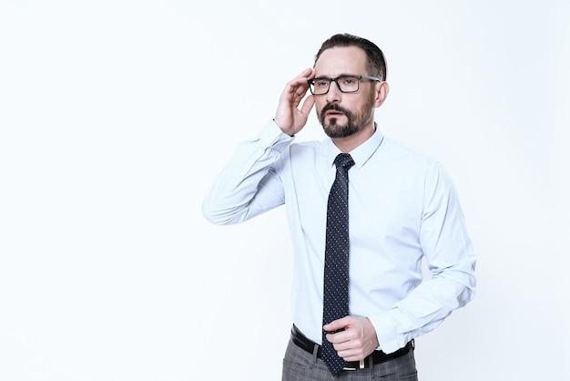 Um homem tem uma dor de cabeça. ele mantém as mãos na cabeça. Foto Premium