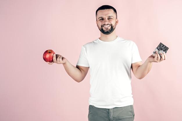 Um homem tem uma maçã e um chocolate nas mãos. alimentos saudáveis e não saudáveis. Foto Premium