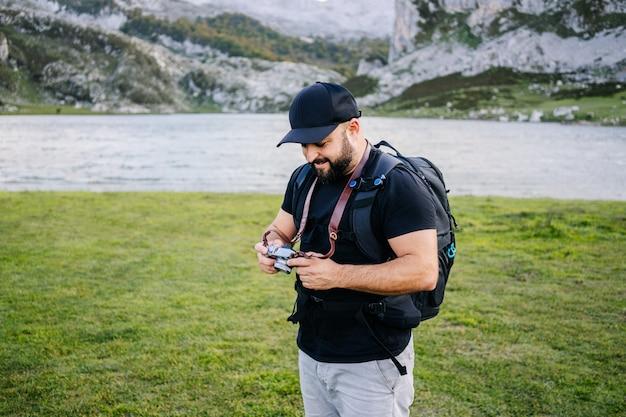 Um homem tira fotos em uma paisagem de montanha Foto Premium
