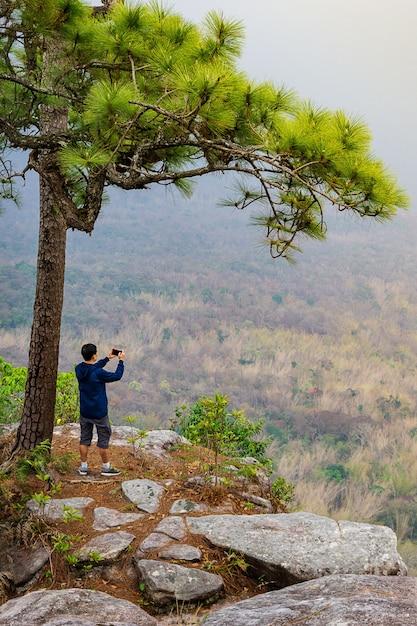 Um homem tirando foto no ponto de vista na beira de um fundo de natureza do penhasco Foto Premium