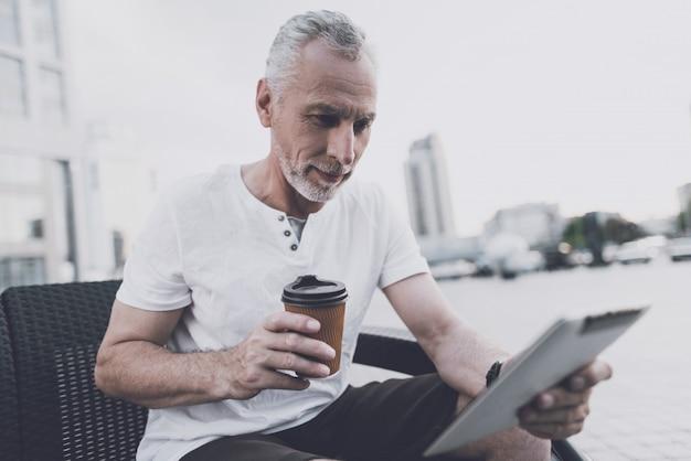 Um homem velho com uma barba senta-se em um sofá na rua Foto Premium