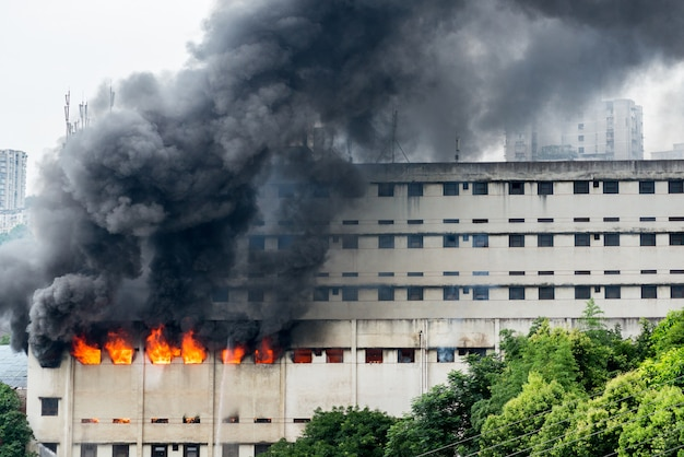 Um incêndio irrompeu no armazém e a brigada de incêndio apagava o fogo. Foto Premium