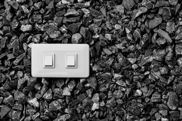 Um interruptor de luz elétrica doméstica branca em um cascalho. Foto Premium