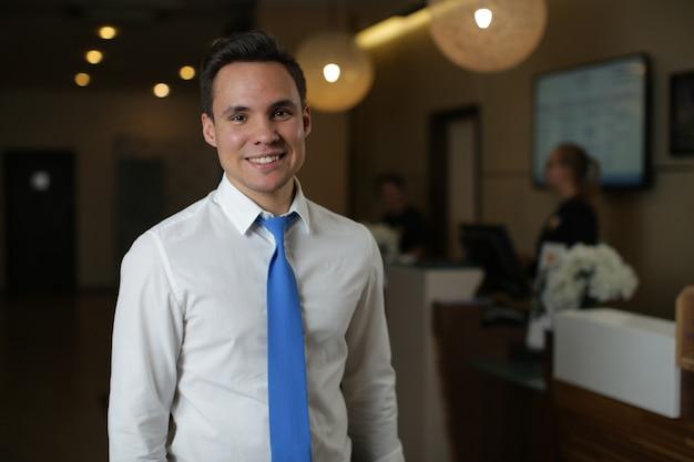 Um jovem administrador de hotel, de camisa branca e gravata azul, fica de pé contra a recepção. Foto Premium