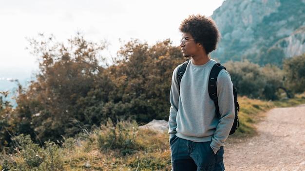 Um jovem africano com as mãos no bolso, olhando a vista Foto gratuita