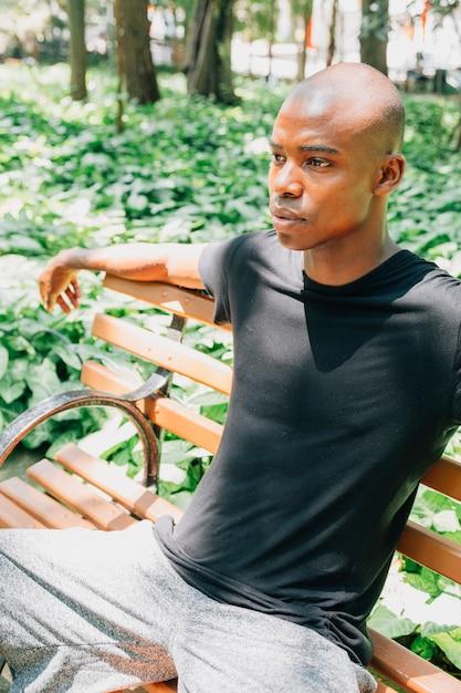 Um jovem africano sentado no banco no jardim Foto gratuita