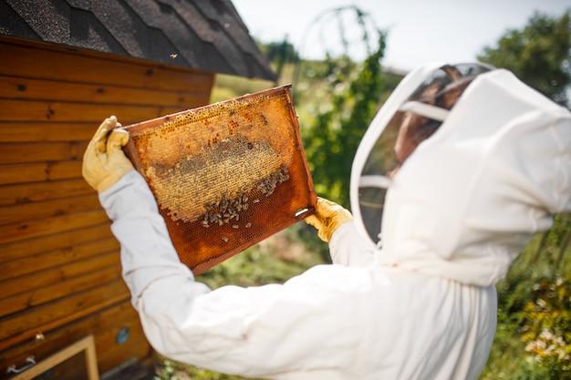 Um jovem apicultor feminino em um traje profissional de apicultor Foto Premium