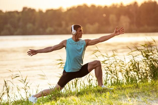 Um jovem atlético malhando ouvindo música à beira do rio ao ar livre Foto gratuita