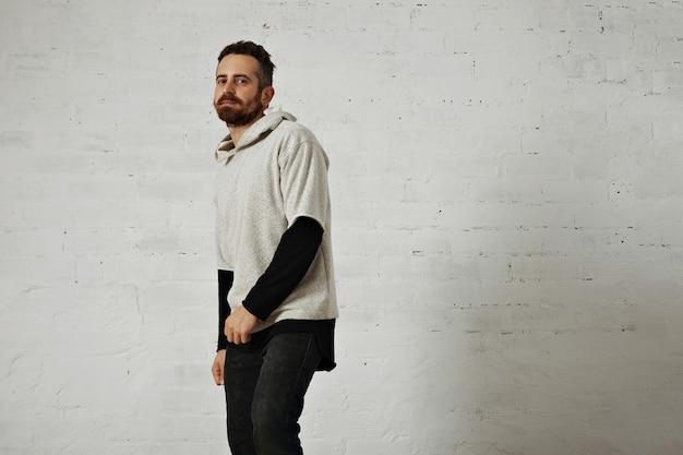 Um jovem barbudo apresentando um moletom macio de algodão liso cinza com jeans preto isolado no branco Foto gratuita