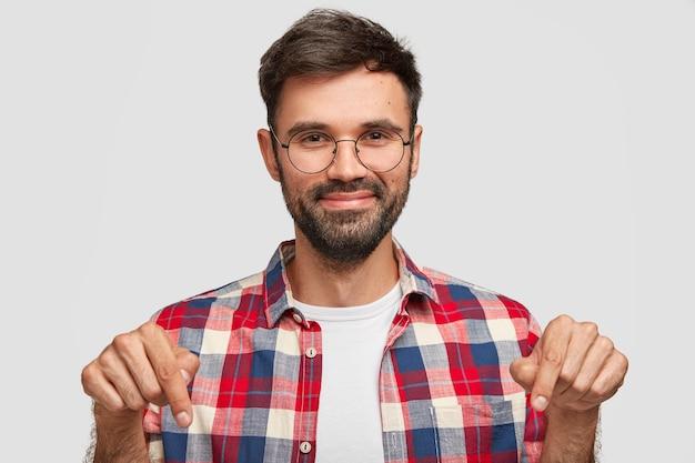 Um jovem barbudo positivo aponta para baixo com uma expressão de satisfação satisfeita e demonstra algo no chão Foto gratuita