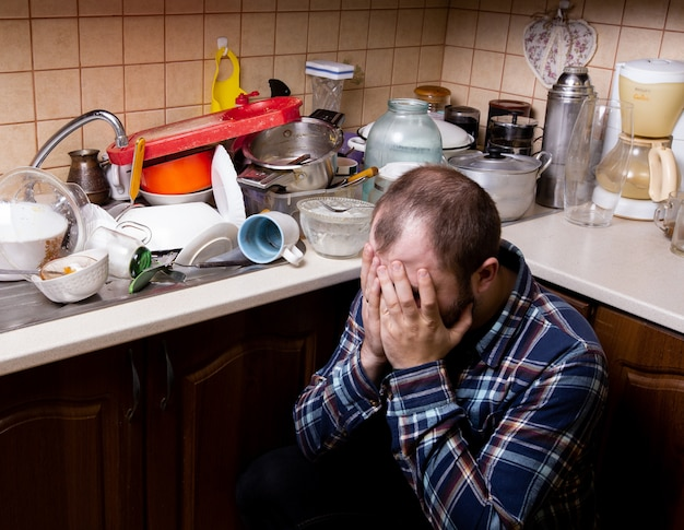 Premium Photo |  A young bearded man sits on the floor and is shocked by the amount of dirty dishes in the kitchen sink to be washed.