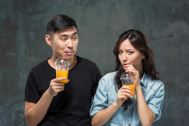 Um jovem casal asiático bonito com um copo de suco de laranja Foto gratuita