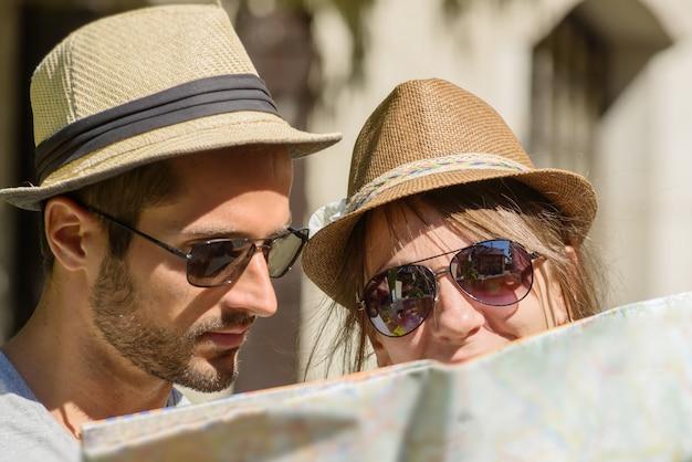 Um jovem casal com chapéus, olhando para um mapa Foto Premium
