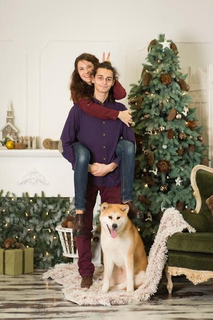 Um jovem casal com um cachorro brincando perto de uma árvore de natal. feliz ano novo e feliz natal Foto Premium