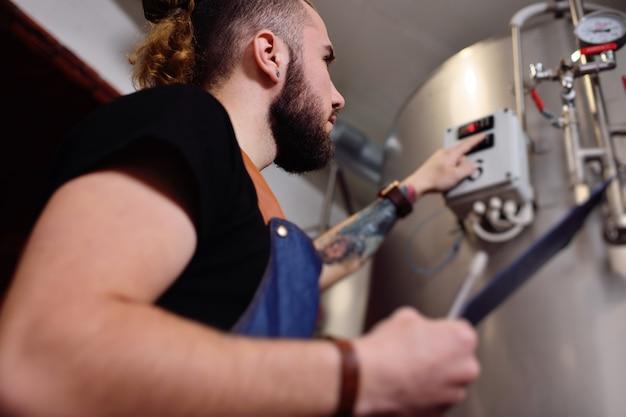 Um jovem cervejeiro atraente com uma barba examina o equipamento para fabricação de cerveja e registra os resultados no papel. Foto Premium