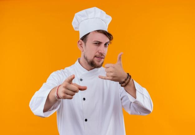 Um jovem chef barbudo confiante em uniforme branco, mostrando um gesto de chamada com a mão enquanto olha para uma parede laranja Foto gratuita