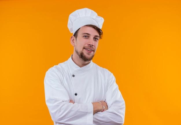 Um jovem chef barbudo feliz e bonito em uniforme branco de mãos postas enquanto olha para uma parede laranja Foto gratuita