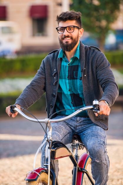 Um jovem com barba, andar pela cidade com bicicleta Foto Premium
