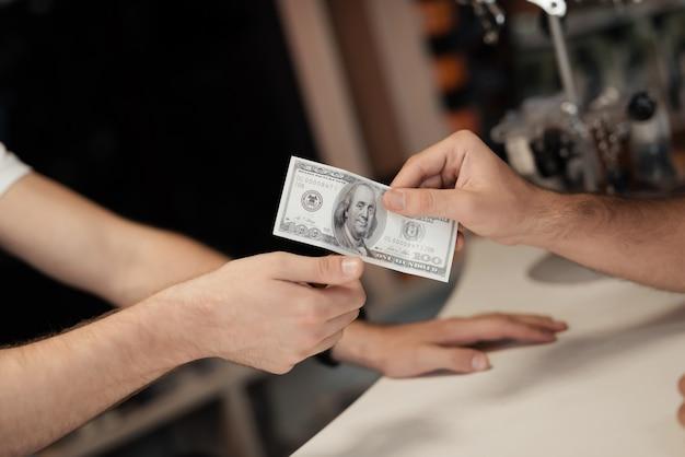 Um jovem dá dinheiro a outro homem. Foto Premium