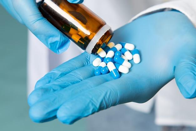 Um jovem de vista frontal na camisa branca e luvas azuis tomando pílulas no espaço azul Foto gratuita