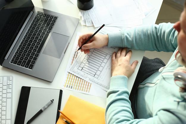 Um jovem designer segura uma caneta de um tablet em sua Foto Premium