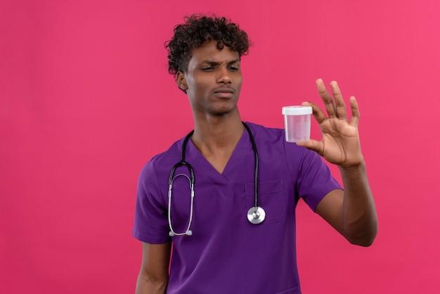 Um jovem e confuso médico bonito de pele escura com cabelo encaracolado, usando uniforme violeta com estetoscópio olhando para um frasco de plástico médico Foto gratuita