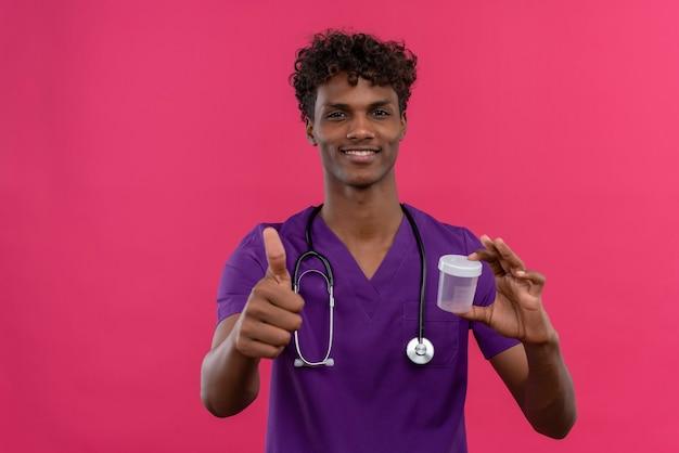 Um jovem e feliz médico bonito de pele escura com cabelo encaracolado usando uniforme violeta com estetoscópio mostrando os polegares para cima enquanto segura um frasco de plástico para amostras Foto gratuita