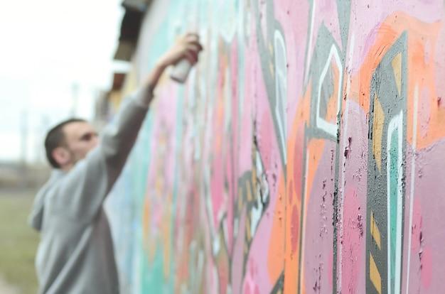 Um jovem em um capuz cinza pinta graffiti em c rosa e verde Foto Premium