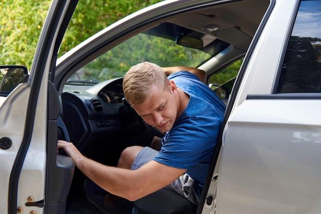 Um jovem em um carro com uma porta aberta e olha para trás. Foto Premium