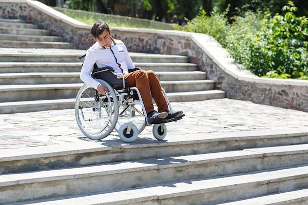 Um jovem em uma cadeira de rodas que não pode descer as escadas. Foto Premium