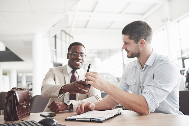 Um jovem empresário negro e atraente compra um carro novo, assina um contrato e leva as chaves ao gerente. Foto gratuita