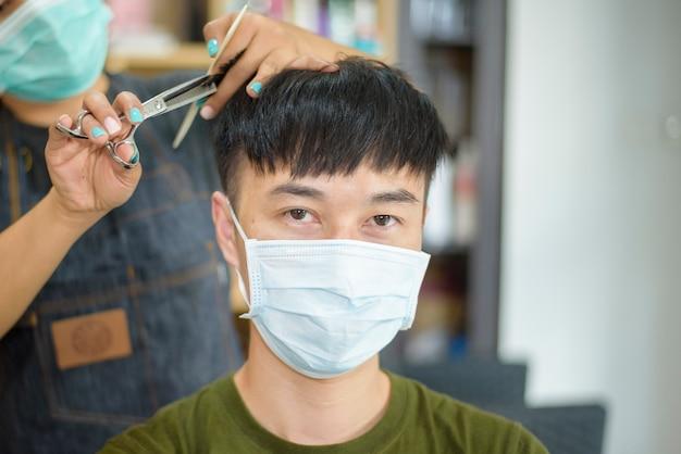 Um jovem está cortando o cabelo em um salão de cabeleireiro Foto Premium