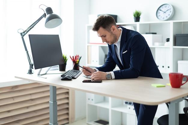 Um jovem fica perto de uma mesa no escritório, segura um lápis na mão e trabalha com documentos e um computador. Foto Premium