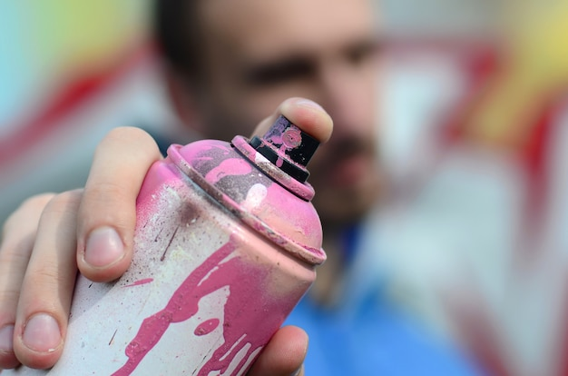 Um jovem grafiteiro em um casaco azul está segurando uma lata de tinta Foto Premium