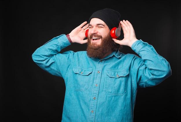Um jovem hippie alegre está ouvindo a música que adora com seus novos fones de ouvido e, gostando, está olhando para longe Foto Premium