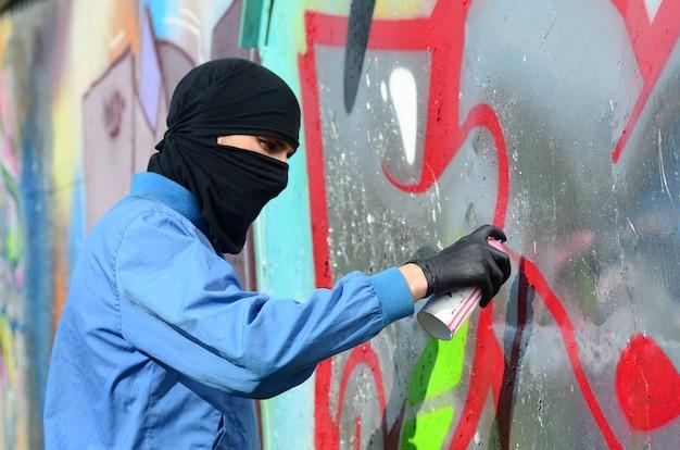 Um jovem hooligan com uma cara escondida pinta graffiti em uma parede de metal. conceito de vandalismo ilegal Foto Premium