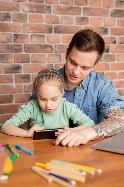 Um jovem pai bonito e sua filha curiosa sentados à mesa e usando o aplicativo móvel no smartphone juntos Foto Premium