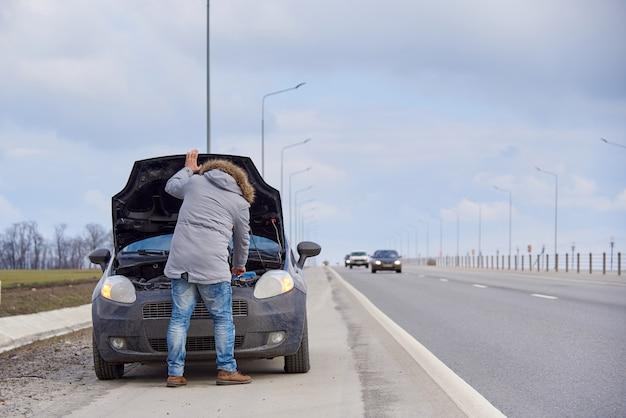 Um jovem perto de carro com um capô aberto na beira da estrada. Foto Premium