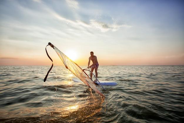 Um jovem rapaz, um atleta levanta uma vela em um windsurf Foto Premium