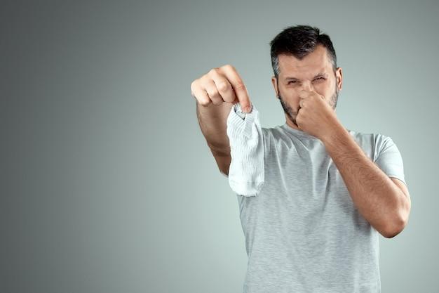Um jovem segura suas meias fedorentas e cobre o nariz com a mão Foto Premium