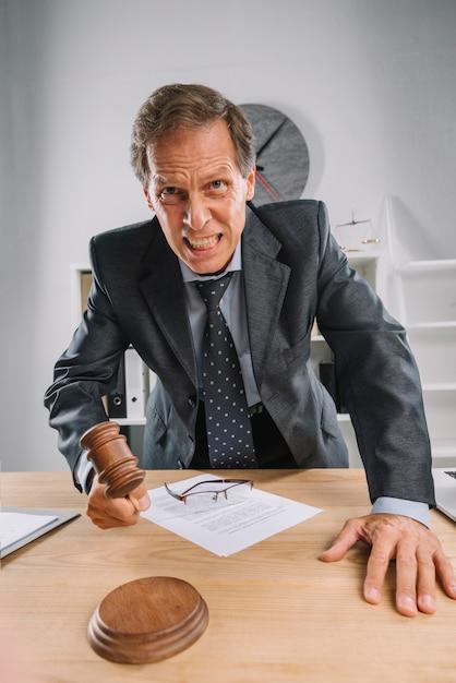 Um juiz maduro com raiva, batendo o martelo na mesa na sala de audiências Foto gratuita