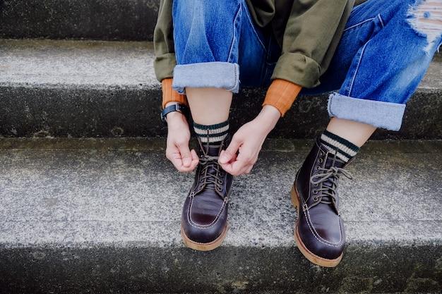 Um laço de mulher hipster atacadores enquanto está sentado na escadaria Foto Premium