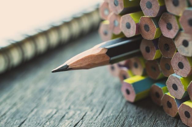 Um lápis aguçado que está para fora do outro lápis novo na tabela de madeira. Foto Premium