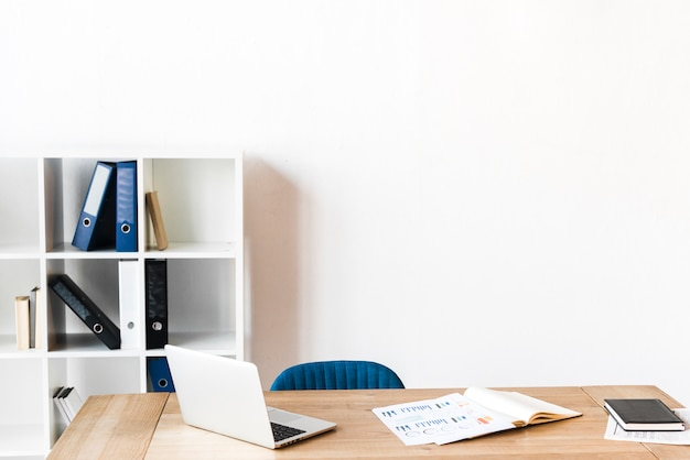 Um laptop aberto e gráfico na mesa de madeira no escritório Foto gratuita